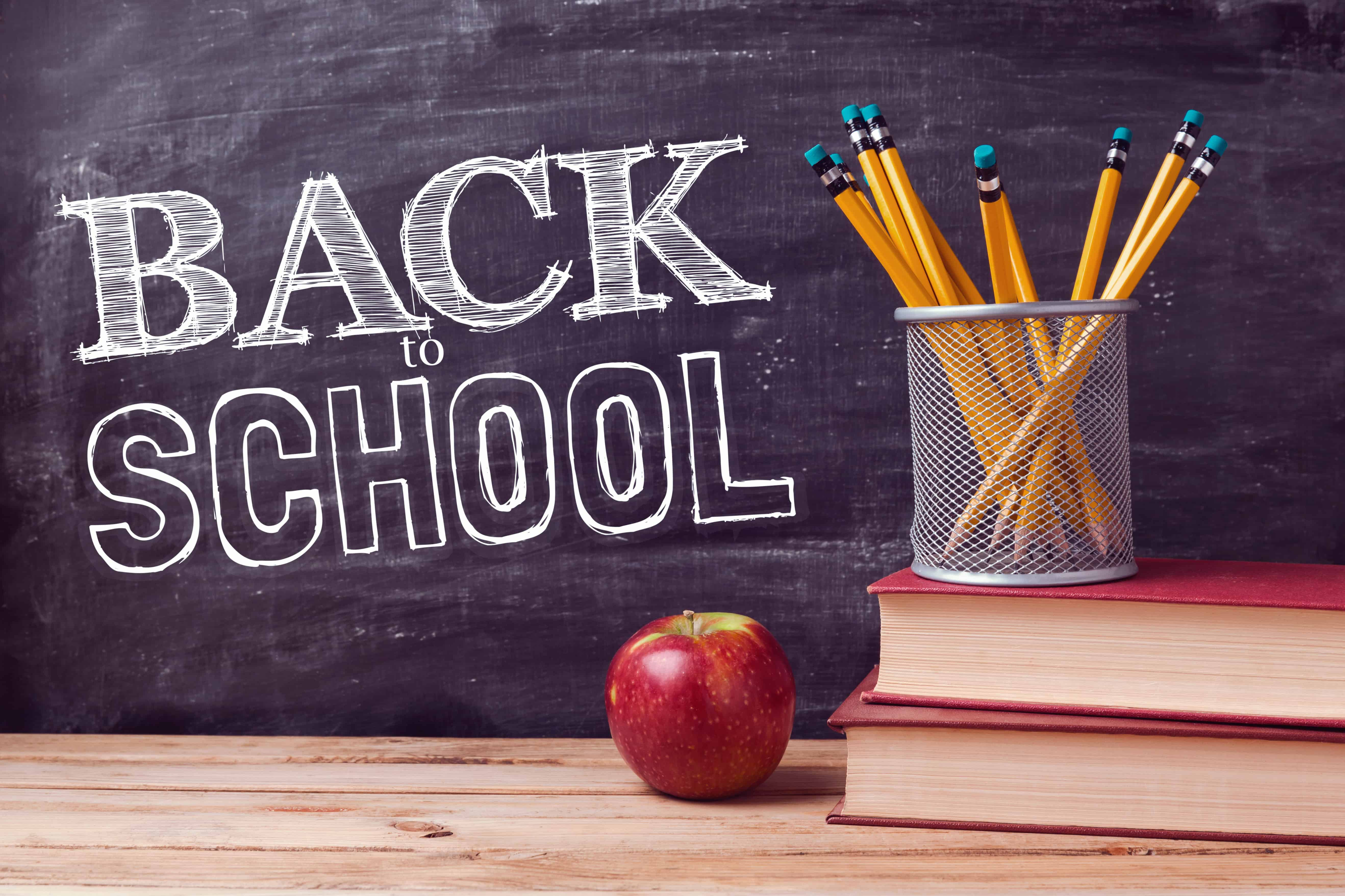 Back To School Lettering With Books Pencils And Apple Over Chalkboard Background